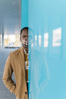 African man standing with hand in pocket behind blue glass wall during COVID-19 - EGAF01788