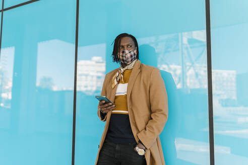 African man in protective face mask with smart phone standing while leaning on blue glass wall - EGAF01791