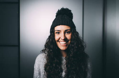 Joyful young woman in knit hat against gray wall - DAMF00728