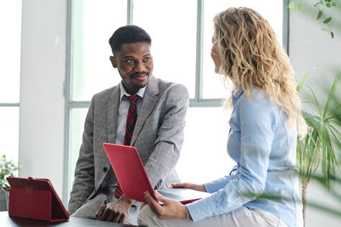 Smiling male entrepreneur sitting by blond woman with laptop while discussing - AGOF00047