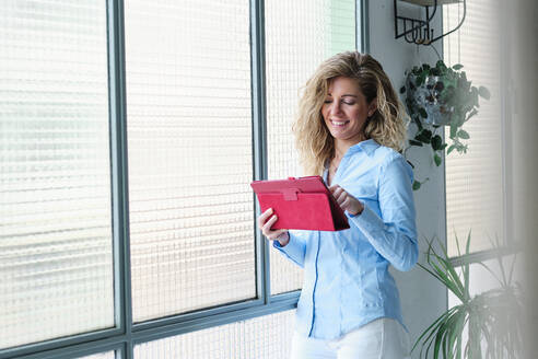 Smiling woman using digital tablet while leaning against glass window - AGOF00050