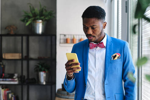 Mid adult man wearing suit while using smart phone - AGOF00059