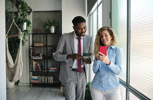 Businessman with coffee cup looking at smart phone held by female colleague while standing by glass window - AGOF00068