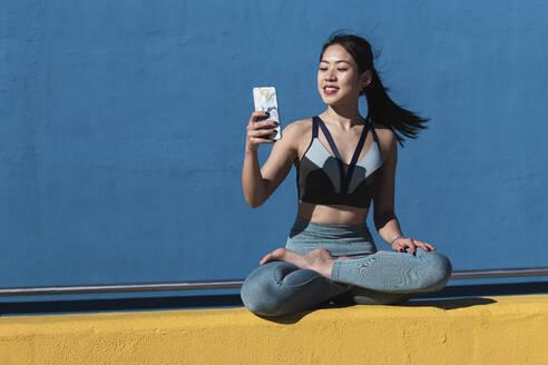 Smiling beautiful woman using mobile phone while sitting cross legged on retaining wall - PNAF00706