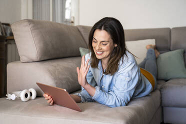 Happy woman talking on video call through digital tablet while lying on sofa at home - AFVF08184