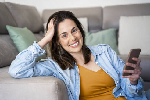 Beautiful smiling woman holding mobile phone while sitting at sofa - AFVF08187