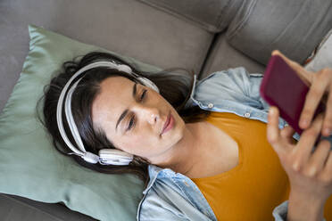 Young woman with headphones using mobile phone while lying on sofa at home - AFVF08190