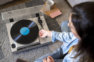 Woman playing record while sitting on carpet at home - AFVF08199