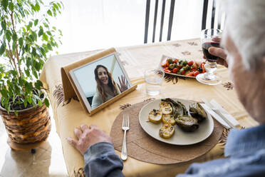 Senior man on video call with daughter while having food at table - AFVF08203
