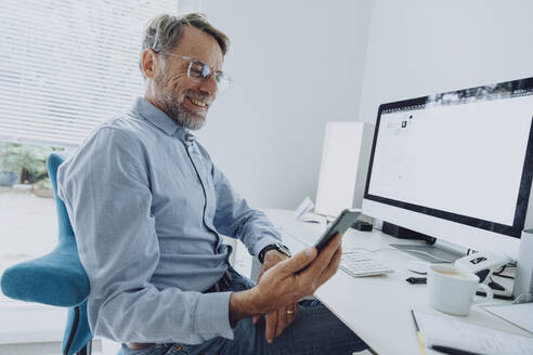 Mature businessman using smart phone while sitting at home office - MFF07208