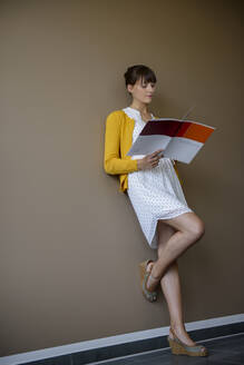 Female entrepreneur reading documents while leaning on wall - BMOF00489