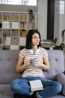 Thoughtful young woman with coffee cup sitting on sofa while looking away - GIOF11343