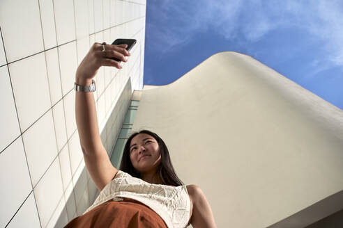Young woman taking selfie with mobile phone on sunny day - VEGF03933