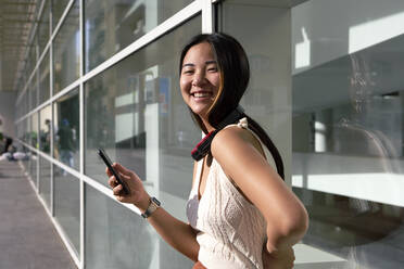 Smiling woman with smart phone and headphones around neck against glass wall - VEGF03945