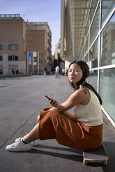 Young woman with smart phone sitting on skateboard during sunny day - VEGF03948