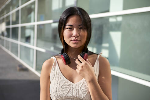 Beautiful woman with headphones around neck on sunny day - VEGF03954