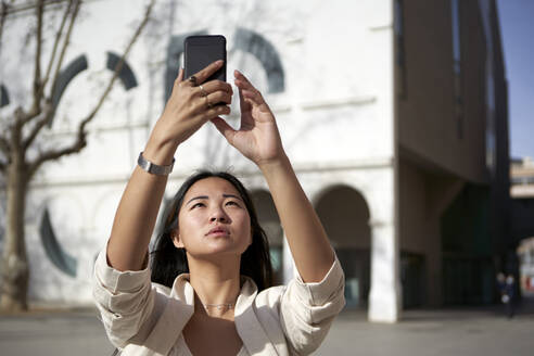 Beautiful woman taking selfie through mobile phone on sunny day - VEGF03957