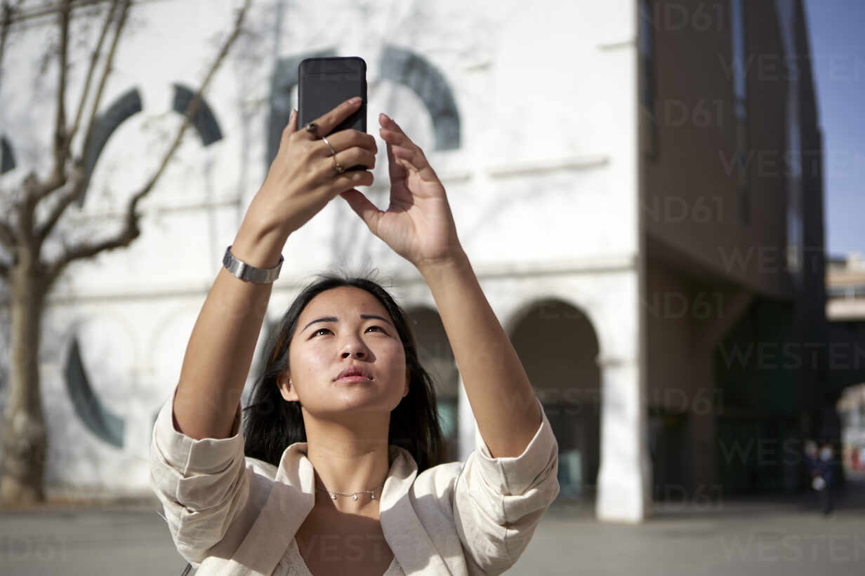 Beautiful woman taking selfie through mobile phone on sunny day - VEGF03957 - Veam/Westend61