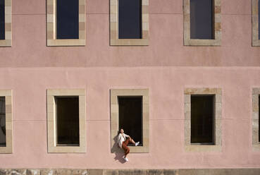 Woman sitting on window sill of building during sunny day - VEGF03963