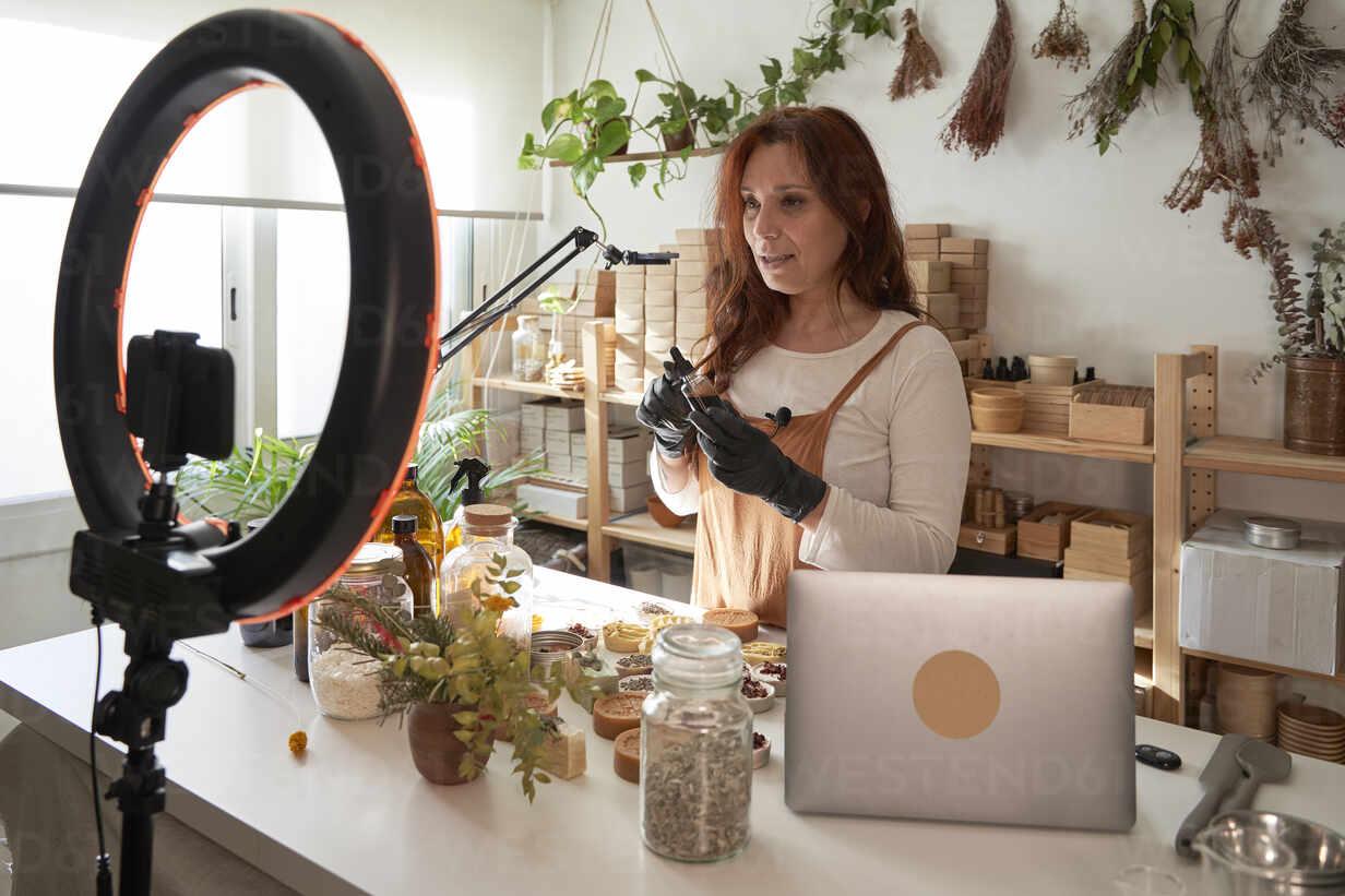 Weibliche Bloggerin erklärt über Produkt durch Video-Tutorial auf Smartphone bei Workshop - VEGF03978 - Veam/Westend61