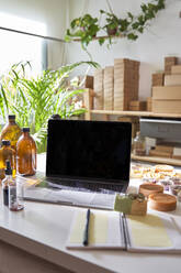 Laptop, note pad, soaps, oils on table at workshop - VEGF03984