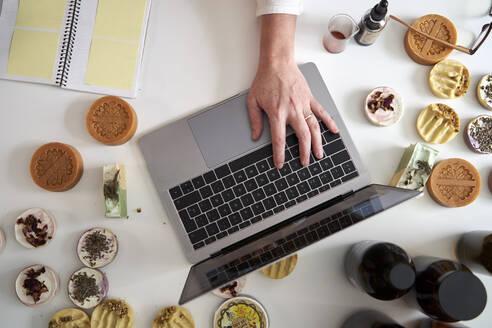 Female entrepreneur's hand typing on laptop over table - VEGF03990