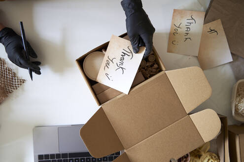 Woman's hands putting thank you label in box at workshop - VEGF03993