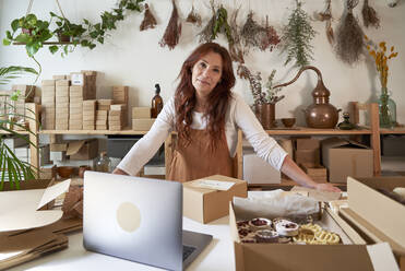 Smiling female entrepreneur leaning on table at workshop - VEGF03999