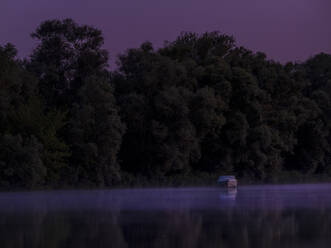 Lone motorboat floating in Saone river at purple night - HAMF00842
