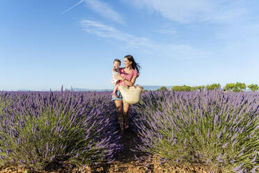 Mother carrying baby daughter in vast lavender field during summer - GEMF04692