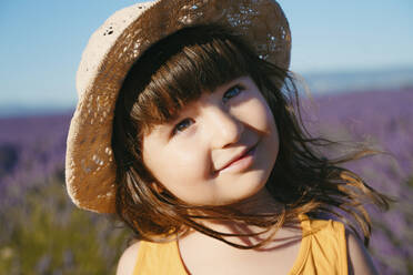 Portrait of cute little girl wearing straw hat standing outdoors - GEMF04695