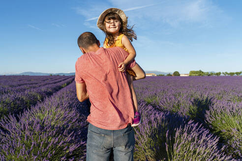 Father carrying baby daughter in vast lavender field during summer - GEMF04698