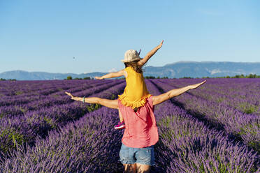 Mother piggybacking little daughter in vast summer lavender field - GEMF04707