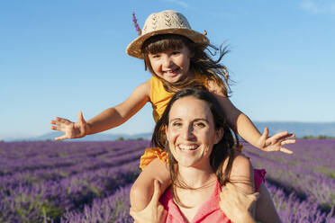 Little girl on shoulders of happy mother in a lavender field at afternoon in Valensole, Provence, France - GEMF04710