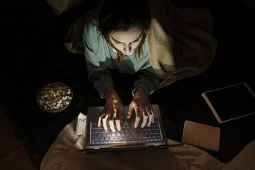 Woman using laptop while lying by popcorn and digital tablet at home - AFVF08209