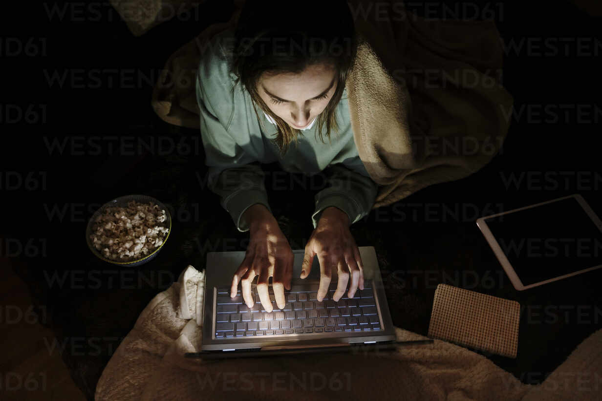 Woman using laptop while lying by popcorn and digital tablet at home - AFVF08209 - VITTA GALLERY/Westend61
