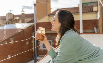 Young woman having fruit smoothie in the morning and waking up, stretching in balcony/terrace - AFVF08212