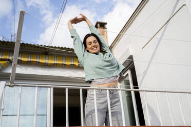 Young woman having fruit smoothie in the morning and waking up, stretching in balcony/terrace - AFVF08218