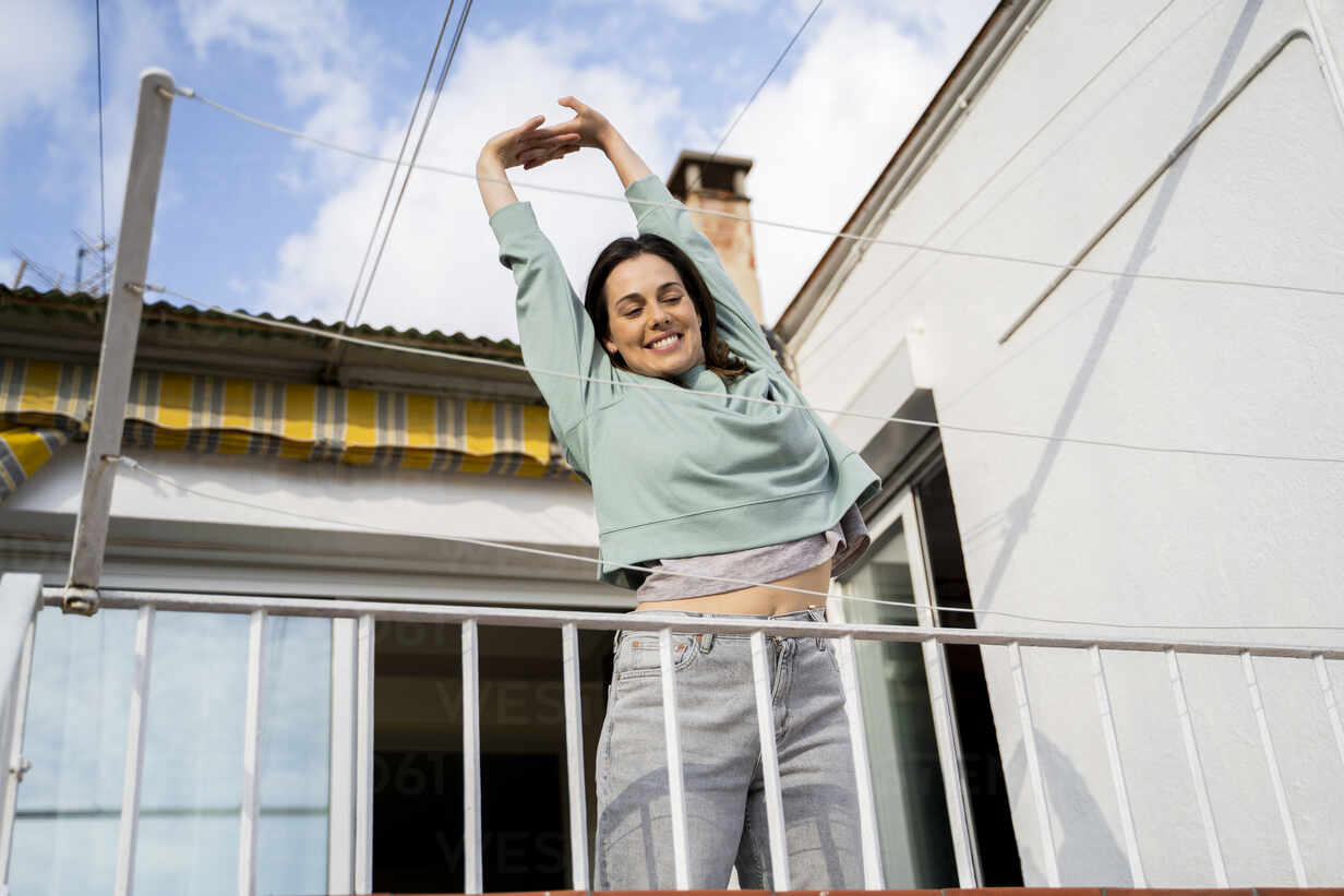 Lächelnde Frau streckt die Hand aus, während sie auf dem Balkon steht - AFVF08218 - VITTA GALLERY/Westend61