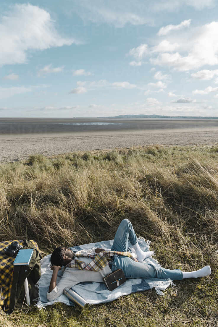 Young man lying on blanket while looking away at beach - BOYF01844 - Boy/Westend61