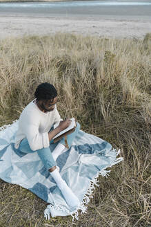 Man sitting on blanket amidst dried plant while writing in diary at beach - BOYF01847