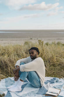 Relaxed young man sitting on blanket amidst dried plant at beach - BOYF01853
