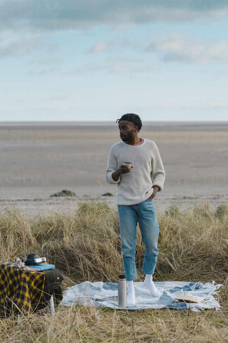 Afrikanischer Mann trinkt Tee, während er am Strand gegen bewölkten Himmel steht - BOYF01862 - Boy/Westend61