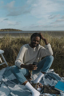 Young man using smart phone while sitting on blanket at beach against cloudy sky - BOYF01868