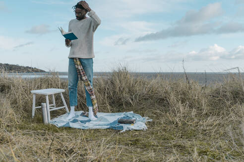 African man reading book while standing amidst dried plants at beach - BOYF01877