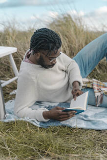 Relaxed young man reading book while lying amidst dried plants - BOYF01883