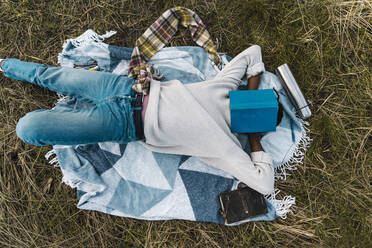 Young man sleeping on blanket while covering his face with book amidst dried plants - BOYF01886