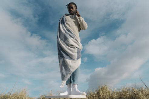 African man wrapped in blanket standing on stool against cloudy sky - BOYF01898
