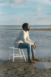 African young man sitting on white tool while watching sunset at beach - BOYF01907