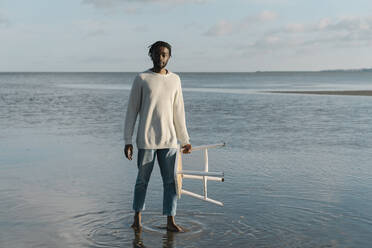 African man with white stool standing at beach against sky - BOYF01916